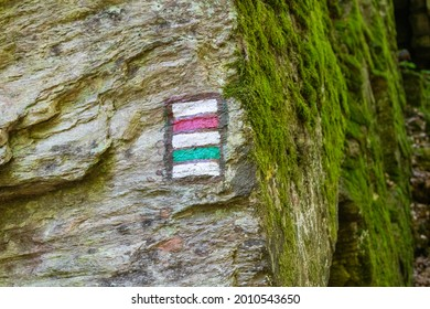 red and green hiking signs painted on a rock