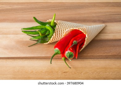 Red and green hot chili peppers in wafer cones on wooden background