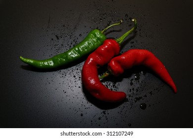 Red and Green Hot Chilli peppers with isolated by black background.