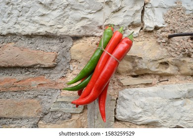 Red and green hot peppers in front of natural stone wall
