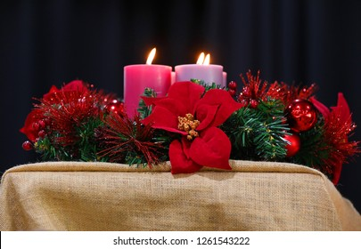 A red and green imitation Christmas wreath decoration with tinsel and poinsettia flowers and large lit candles and flame. Xmas concept with plain black curtain background and simple hessian table