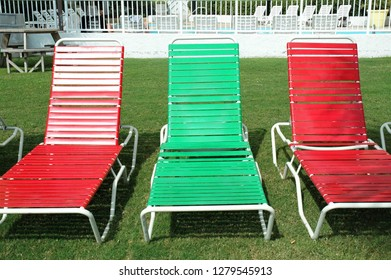 Red and green lounge chairs lined up on the grass.