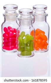 Red, green and orange jelly beans in glass jars on white background