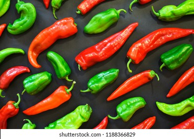 Red and green peppers shapes pattern on a dark background. Vegetables and food abstract background. Top view. Organic food and shapes.