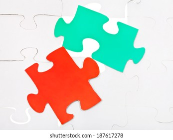 red and green pieces on layer of assembled white puzzles