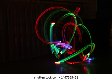 Red, Green, and Rainbow Light Trails on a black background