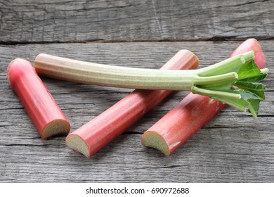 Red and green rhubarb stacks on wooden board