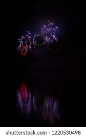 Red and green rings of rich fireworks over surface of Brno's Dam with reflection on the surface of lake
