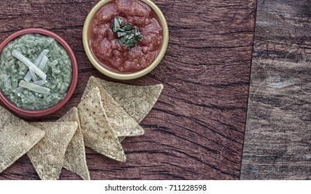 Red and green salsa with tortilla chips on wood background. Stylised grunge, vintage composition.