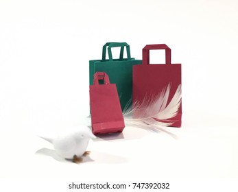 Red and green shopping bags standing against white background with bird and feather props. Christmas theme. On-line shopping concept. Blurred, soft focus.