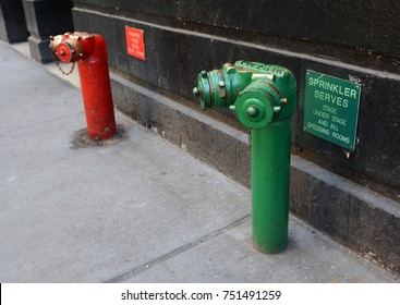 Red and green siamese standpipes on a sidewalk with theatre-related information signs