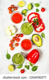 Red and Green vegetable smoothie with ingredients on white table. Top view.