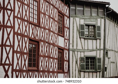 Red and green walls of medieval urban building in french city
