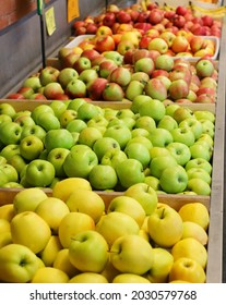 Red green and yellow apples sold in a fruit market stall
