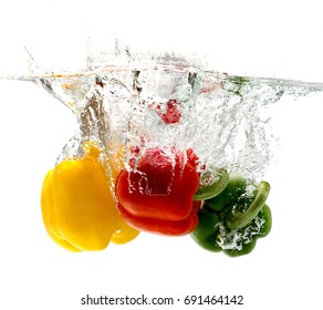 red, green, yellow bell pepper falls to the water, causing bubbles and scattered water.