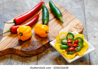 Red, green and yellow hot peppers on wooden board with sliced peppers in white bowl on old wooden table