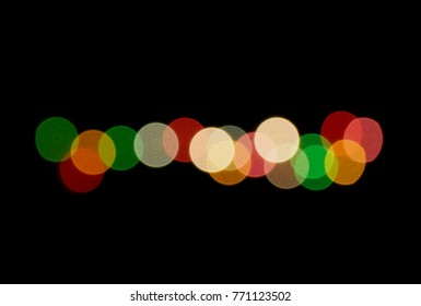 Red green yellow orange Christmas lights over black with copy space