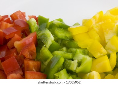 red, green and yellow pepper diced and ready for cooking,  macro shot against white background
