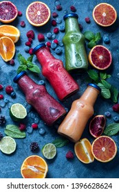 Red, green and yellow smoothies with oranges and mint, healthy vitamin drink in bottles top view