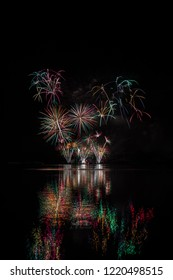 Red, green and yellow stars from rich fireworks over Brno's Dam with lake reflection