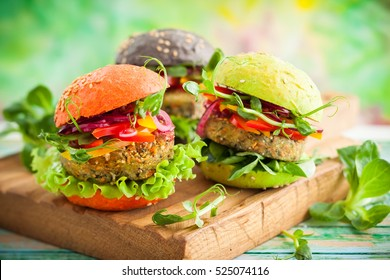 Red, green,black mini burgers with quinoa and vegetables .