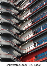 Red and grey coloured metal staircase going up the side of a shopping centre building on the outside