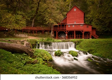 Red gristmill and waterfall located in rural Missouri.