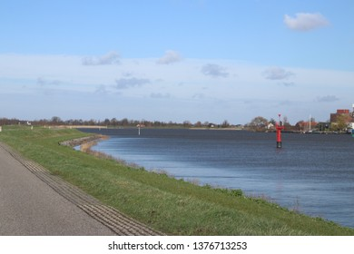 Red guiding post in the river Hollandsche IJssel to mark the safe waterway in the water