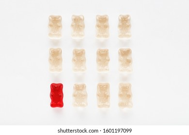 Red gummy bear standing out of the crowd with its distinctive color. Diversity and difference