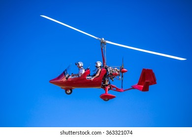 Red gyroplane in flight