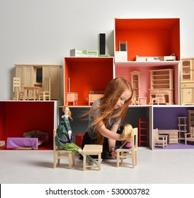 Red hair Baby Girl Kid playing with doll house stuffed with mini furniture toys and doll sitting on a cube in play room at home or kindergarten happy