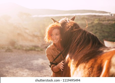 red hair beautiful alternative lady hug her best friends animal horse during the sunset in the country side. backlight in background and love concept, different couple