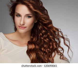 Red Hair. Beautiful Woman with Curly Long Hair. High quality image.