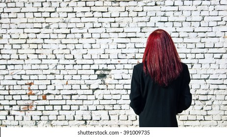 Red hair boy captured on white wall front. Vibrant red hair, white bricks and black coat