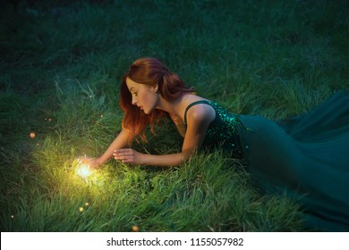 red hair charming woman is lying on the grass in a wonderful emerald dress with long train
