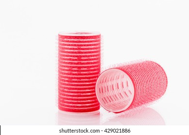 Red hair curlers on white background