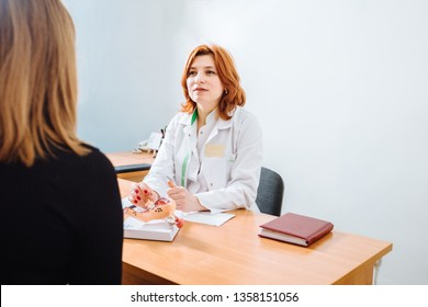 Red hair doctors appointment physician shows to patient shape of uterus with focus on hand with organ. Scene explaining patient causes and localization of diseases of uterus, reproductive system