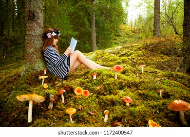 Red hair girl with book and mushrooms in  the forest, Dalarna county, Sweden, summer holidays on the road north europe, northern light. Reading book.