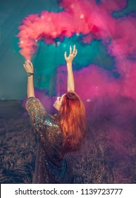 Red Hair girl with colourful smoke grenade has both hands in the air