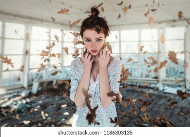 Red hair girl with freckles standing in the falling autumn leaves. Autumn concept. psychical deviations
