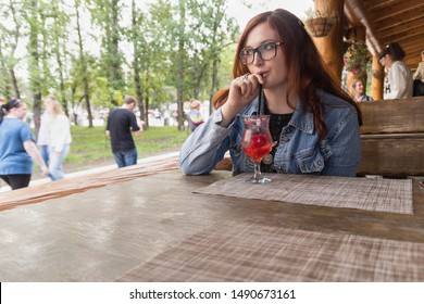 Red hair girl with glasses and a denim jacket sits in a street cafe and drinks a cocktail from a stylish glass through a straw