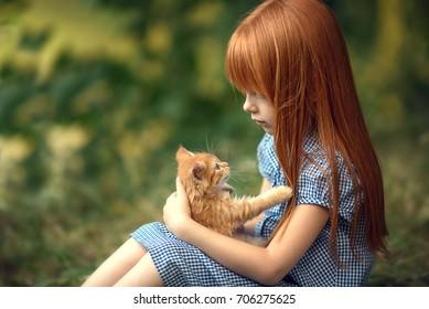 red hair girl holding a ginger kitten