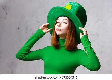Red hair girl in Saint Patrick's Day leprechaun party hat having fun isolated on grey grunge background