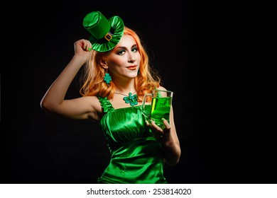 Red hair girl in Saint Patrick's Day leprechaun party hat having fun, holding a mug of ale