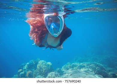 Red hair girl underwater in tropical sea. Snorkel in full face mask. Female swimmer with loose red hair. Beautiful girl in water. Underwater photo shot in ocean. Tropical vacation activity or sport