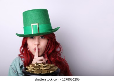 Red hair girl wearing a green Leprechaun's hat shushing while holding a black pot full of gloden coins