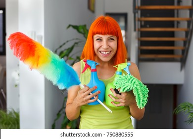 Red hair housewife cleaning her home with a duster