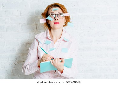 red hair woman in glasses with stickers on her, concentratedly looking up with a sad emotion, and writting in notebook a lot of things to do. White brick wall with shadow behind her.