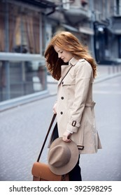 red hair woman in trench is standing in the street