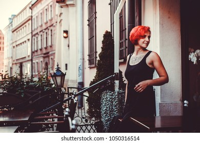 Red hair young woman walking on the old streets of Cracow, Poland